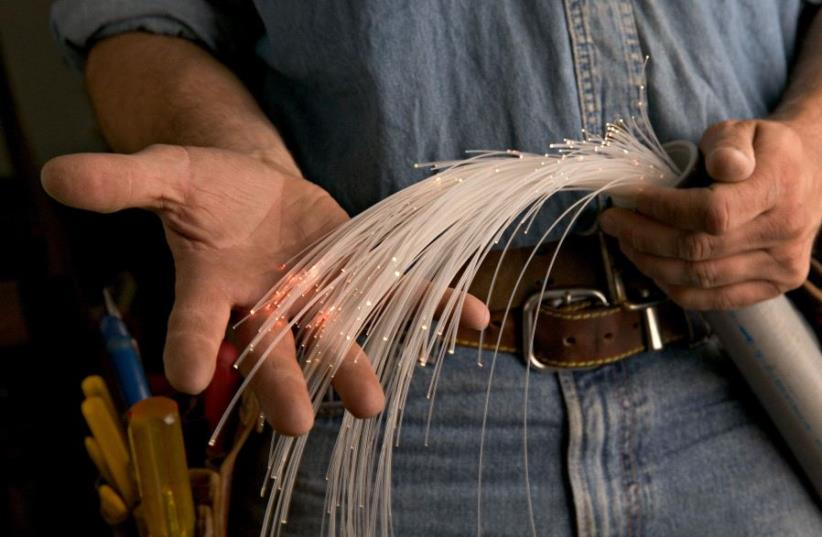 A worker holding a fiber optic cable (photo credit: INGIMAGE PHOTOS)