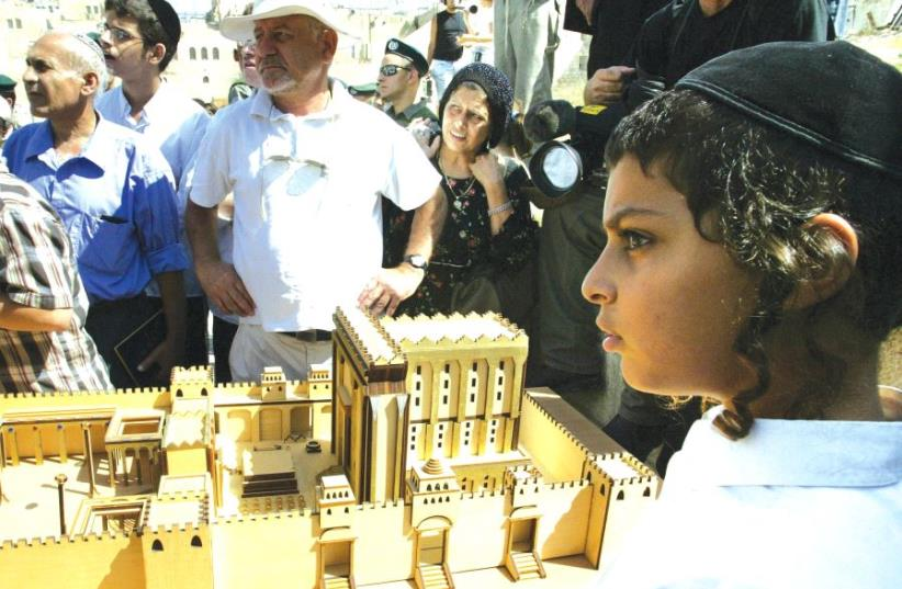 A young boy stands by a model of the Second Temple during a demonstration by Jewish ultra-right-wing protesters at the Western Wall on Tisha Be'av, 2003 (photo credit: REUTERS)