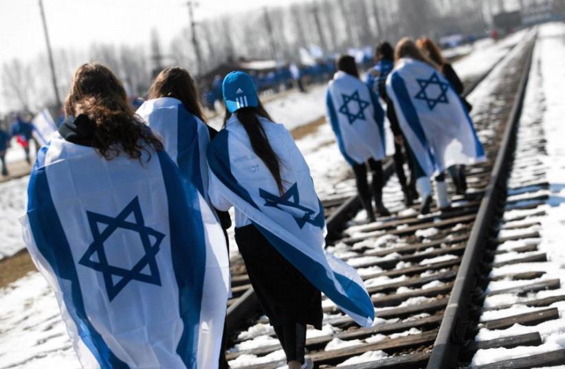 People wear Israeli flags around their shoulders as they walk on the railroad tracks inside the former Nazi death camp of Birkenau (Auschwitz II) in Oswiecim-Brzezinka, southern Poland April 8, 2013. (photo credit: REUTERS/JAKUB OCIEPA/AGENCJA GAZETA)