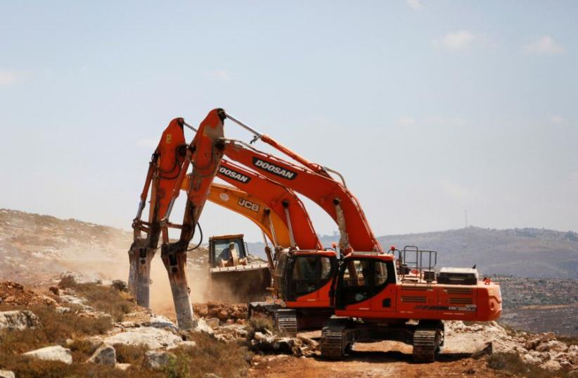 Heavy machinery work on a field as they begin construction work of Amichai, a new settlement which will house some 300 Jewish settlers evicted in February from the settlement of Amona, in the West Bank June 20, 2017. (photo credit: REUTERS/Ronen Zvulun)