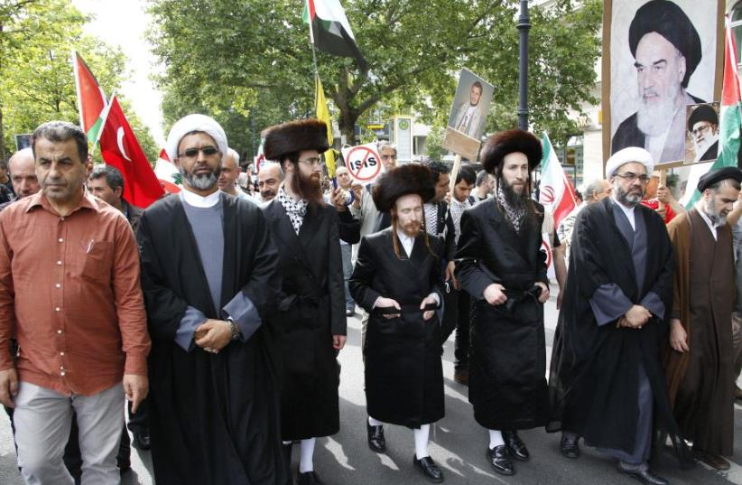 Muslim clerics and anti-Zionist orthodox Jews walk together during the annual al-Quds Day march in Berlin, Germany, July 11, 2015 (photo credit: REUTERS/FABRIZIO BENSCH)