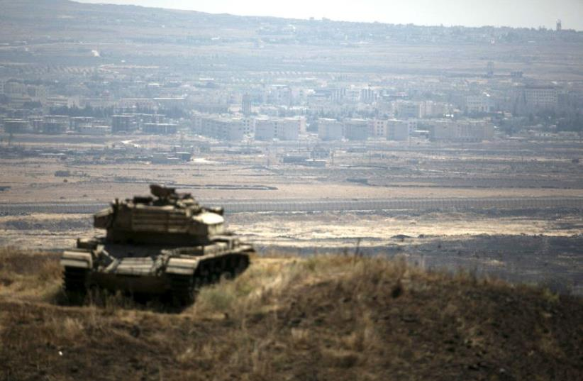 The Syrian area of Quneitra is seen in the background as an out-of-commission Israeli tank parks on a hill, near the ceasefire line between Israel and Syria, in the Golan Heights. (photo credit: BAZ RATNER/REUTERS)