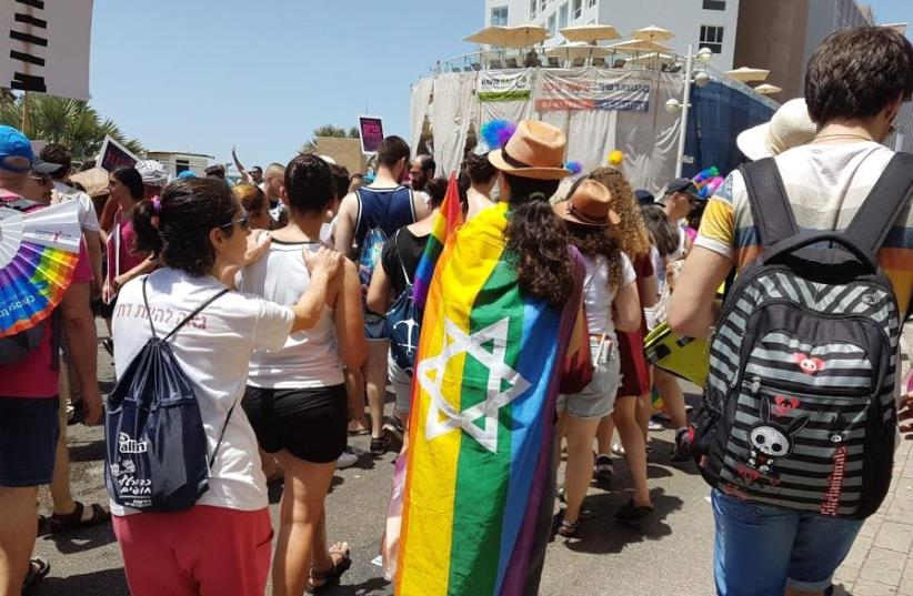 Participant with Jewish Pride flag walking in the 2017 Tel Aviv Pride Parade (photo credit: BECKY BROTHMAN)