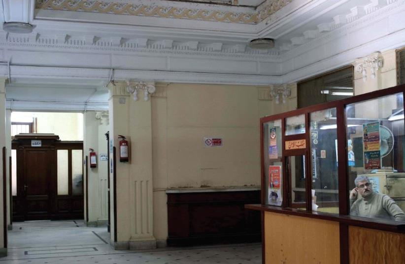 A MAN sits in a security booth at the Nile Company for Medicine on Fouad Street in Alexandria last year. The building was previously a bank owned by Jewish Egyptian-Greek businessman Youssif Adda and is located in an area that used to be known as the Greek-Jewish quarter of the city (photo credit: REUTERS)