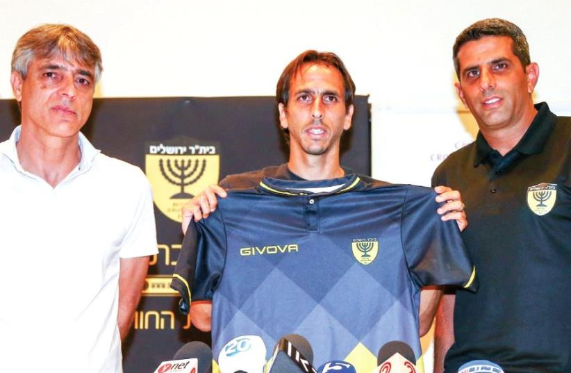 New Beitar Jerusalem midfielder Yossi Benayoun (center) poses with the team's shirt alongside head coach Sharon Mimer (right) and club boss Eli Ohana during yesterday's press conference in Jerusalem. (photo credit: DANNY MARON)