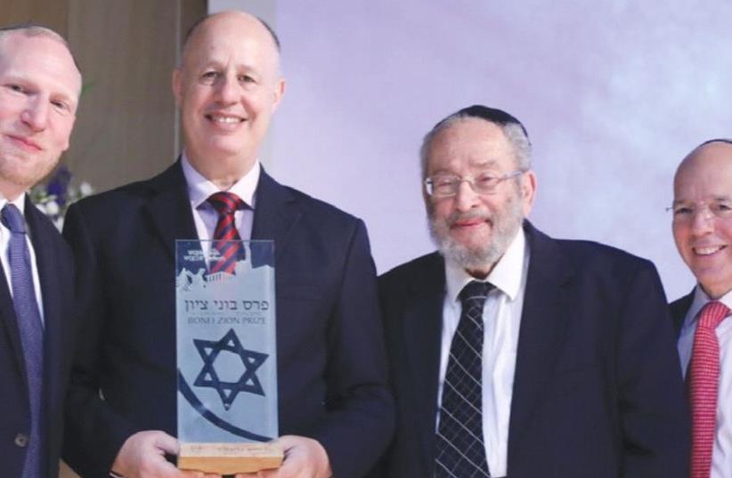 RABBI CHAIM BROVENDER (second right) looks to receive his award, accompanied by Regional Cooperation Minister Tzachi Hanegbi (center) and Nefesh B'Nefesh cofounders Rabbi Yehoshua Fass (left) and Tony Gelbart. (photo credit: KNESSET)