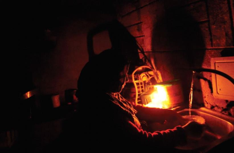 A Palestinian woman washes by candlelight during a power cut in the kitchen of her home in Beit Lahiya in the northern Gaza Strip (photo credit: REUTERS)