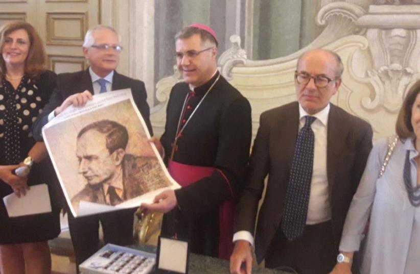 PALERMO ARCHBISHOP Corrado Lorefice holds a portrait of Raoul Wallenberg yesterday, together with (from left) Silvia Constantini and Guillermo Bruschtein of the Raoul Wallenberg Foundation alongside Giulio DiSegni and Evelyn Aouate of the Union of Italian Jewish Communities (photo credit: TAMARA ZIEVE)