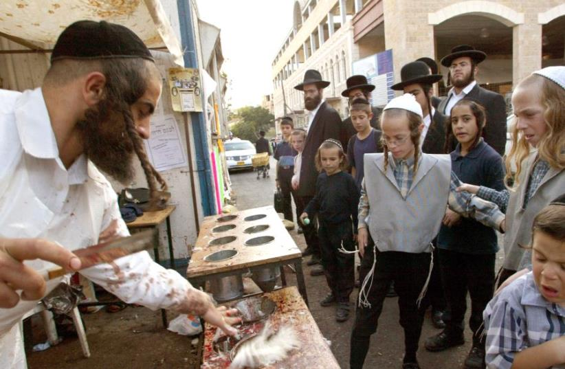 DATE IMPORTED: October 07, 2003 Group of ultra-Orthodox Jews watch a butcher put drain the blood from a slaughtered chickens in the Mea Shearim neighbourhood in Jerusalem October 2 2003 (photo credit: REUTERS/GIL COHEN MAGEN)