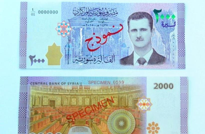 A portrait of Syria's President Bashar Assad is seen printed on the new Syrian 2,000-pound banknote that went into circulation on Sunday, in this handout picture provided by SANA on July 2, 2017, Syria. (photo credit: REUTERS)