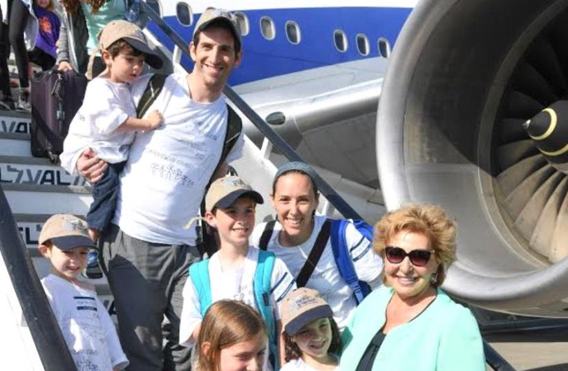 The Bienenfeld family from Plainview, NY getting off the plane in Tel Aviv with Minister of Aliyah and Integration Sofa Landver. (photo credit: SHAHAR AZRAN COURTESY OF NEFESH B'NEFESH)