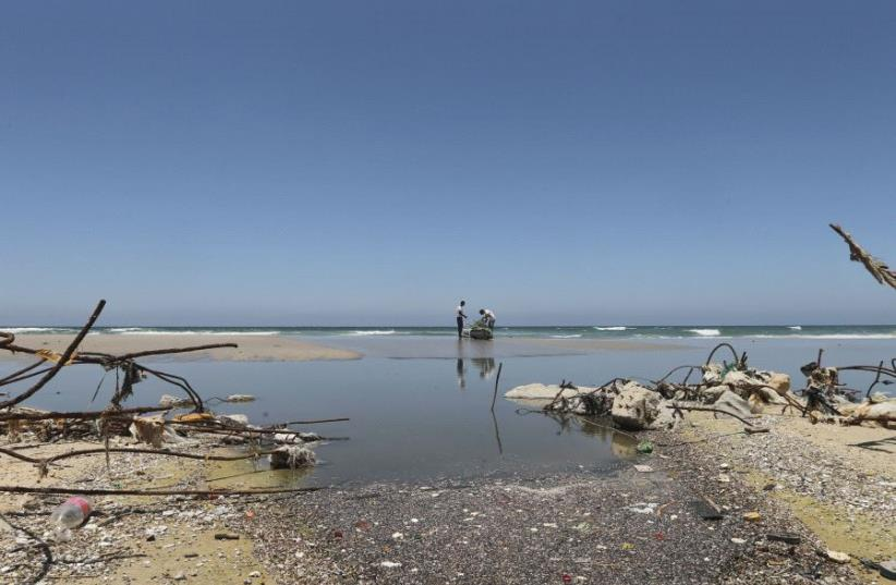 Palestinian fishermen are reflected in wastewater as they prepare their boat on a beach in the central Gaza Strip June 26, 2014. (photo credit: REUTERS/MOHAMMED SALEM)