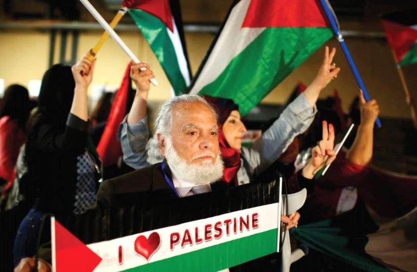 PEOPLE HOLD Palestinian flags during the Conference of Palestinians in Berlin in 2015. (photo credit: REUTERS)