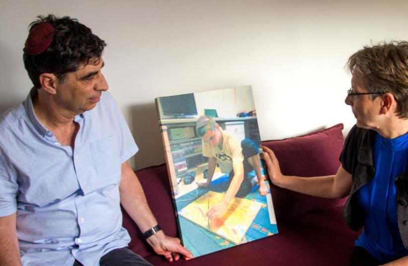 Simha and Leah Goldin with a   photo of Hadar doing one of the activities he loved - painting - his last piece before he was killed. (photo credit: LAURA BEN-DAVID)