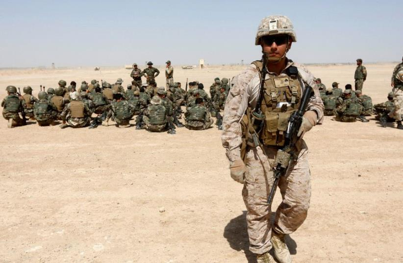 A US Marine walks near Afghan National Army (ANA) soldiers during training in Helmand province, Afghanistan, July 5, 2017. (photo credit: REUTERS/OMAR SOBHANI)