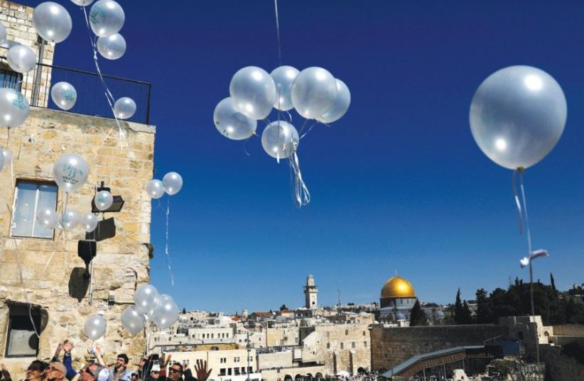 Visitors release balloons as they begin celebrating a bar mitzva near the Western Wall in Jerusalem in February (photo credit: REUTERS)