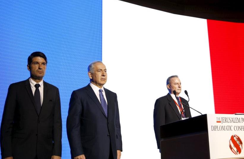Israeli Prime Minister Benjamin Netanyahu (C) and former French Ambassador to Israel Patrick Maisonnave (L) observe a moment of silence to pay tribute to victims of the November 2015 Paris attacks, during the Jerusalem Post Diplomatic Conference in Jerusalem. (photo credit: REUTERS/Ronen Zvulun)
