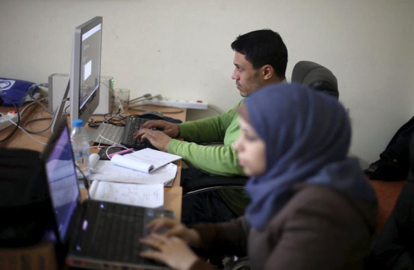 Young Palestinian entrepreneurs use their computers in Gaza City [File] (photo credit: IBRAHEEM ABU MUSTAFA / REUTERS)