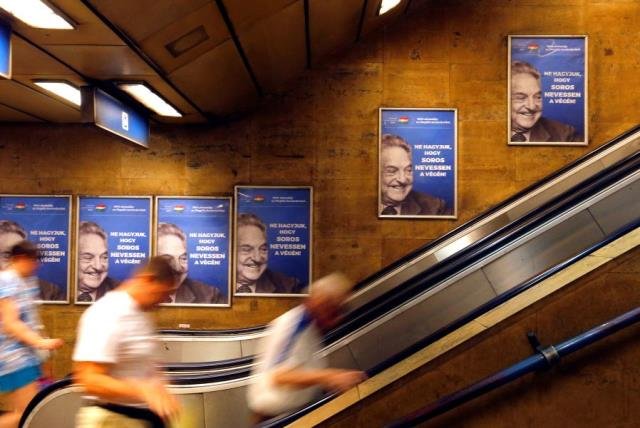 """Hungarian government poster portraying financier George Soros and saying """"Don't let George Soros have the last laugh"""" is seen at an underground stop in Budapest, Hungary July 11, 2017.  (photo credit: REUTERS/LASZLO BALOGH)"""