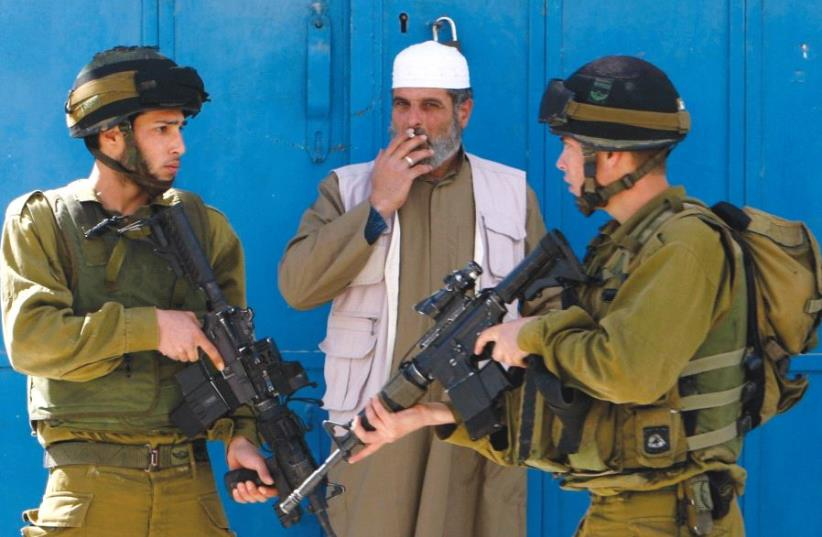 A Palestinian man smokes a cigarette beside Israeli soldiers after minor clashes with Palestinian stone-throwers in the West Bank city of Hebron February 23, 2010 (photo credit: REUTERS/AMMAR AWAD)