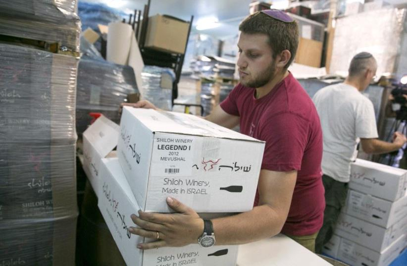 A worker carries boxes containing wine bottles for export at Shiloh Wineries, north of the West Bank city of Ramallah November 8, 2015. (photo credit: REUTERS/BAZ RATNER)
