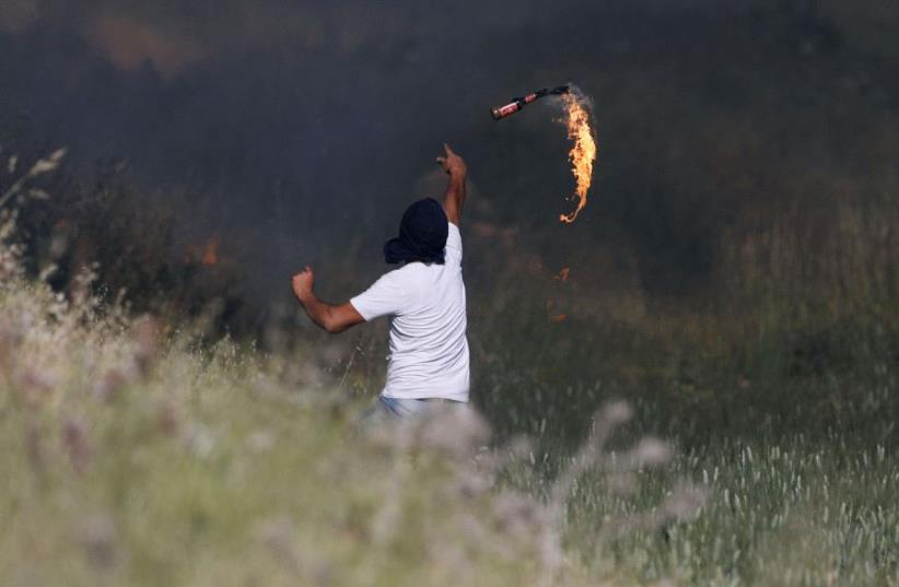 A Palestinian protester hurls a molotov cocktail towards Israeli troops during clashes at a protest in support of Palestinian prisoners on hunger strike in Israeli jails, near the Jewish settlement of Beit El, near the West Bank city of Ramallah May 11, 2017. (photo credit: REUTERS/MOHAMAD TOROKMAN)