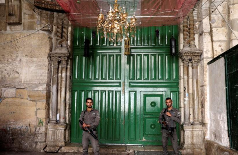 Israeli border policemen secure the entrance to the compound known to Jews as Temple Mount, in Jerusalem's Old City July 14, 2017. (photo credit: REUTERS/AMMAR AWAD)