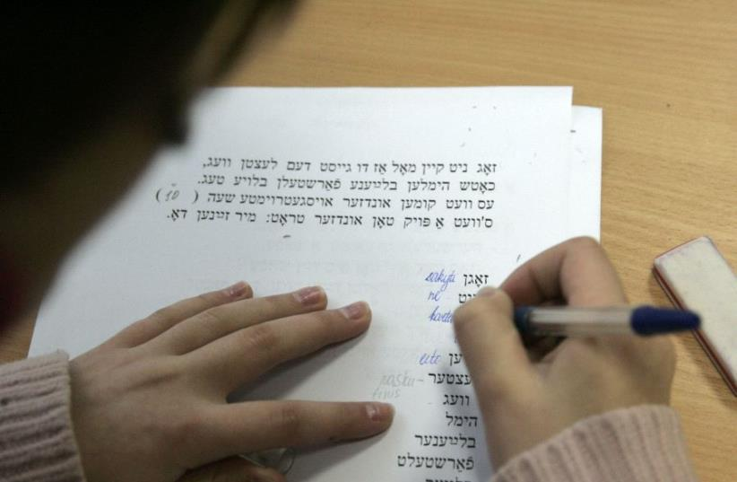 A secondary school student learns Yiddish during a lesson of Jewish history and culture at Solomo Aleichemo Jewish school in Vilnius, Lithuania (photo credit: REUTERS/INTS KALNINS)