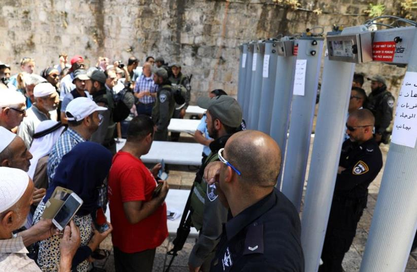 Palestinians stand in front of Israeli police officers and newly installed metal detectors at an entrance to the  Temple Mount, in Jerusalem's Old City July 16, 2017. (photo credit: REUTERS)