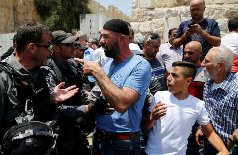 A Palestinian argues with an Israeli border police officer during scuffles that erupted after Palestinians held prayers just outside Jerusalem's Old City in protest over the installation of metal detectors placed at an entrance to the Temple Mount, July 17, 2017.  (photo credit: REUTERS)
