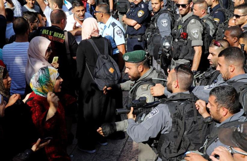 A Palestinian woman argues with an Israeli border policeman at the entrance to the compound known to Muslims as Noble Sanctuary and to Jews as Temple Mount, in Jerusalem's Old City  (photo credit: AMMAR AWAD / REUTERS)