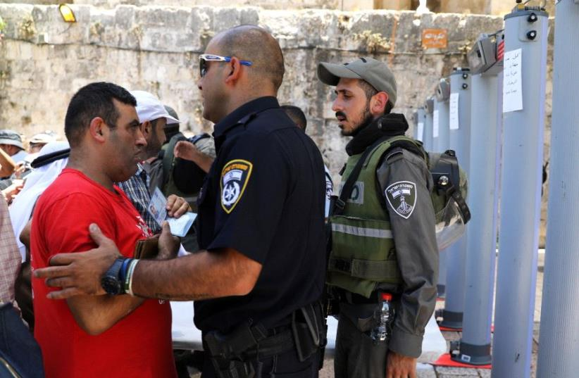 An Israeli police officer checks the identity of a Palestinian man next to newly installed metal detectors at an entrance to the compound known to Muslims as Noble Sanctuary and to Jews as Temple Mount, in Jerusalem's Old City July 16, 2017. (photo credit: AMMAR AWAD / REUTERS)