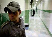 A prison guard stands along a corridor in Tehran's Evin prison June 13, 2006.