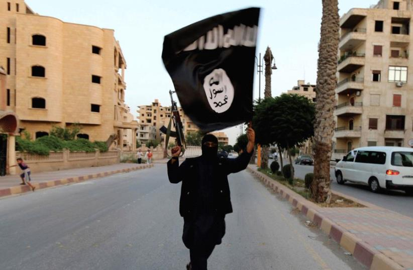 A MEMBER of ISIS waves the group's flag in Raqqa (photo credit: REUTERS)