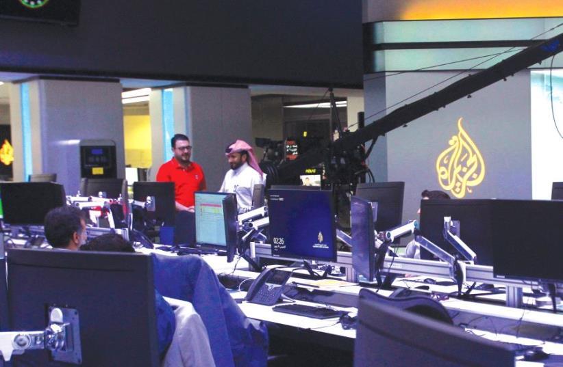 Staff work inside the headquarters of Al Jazeera Media Network, in Doha, Qatar, last month. (photo credit: REUTERS)