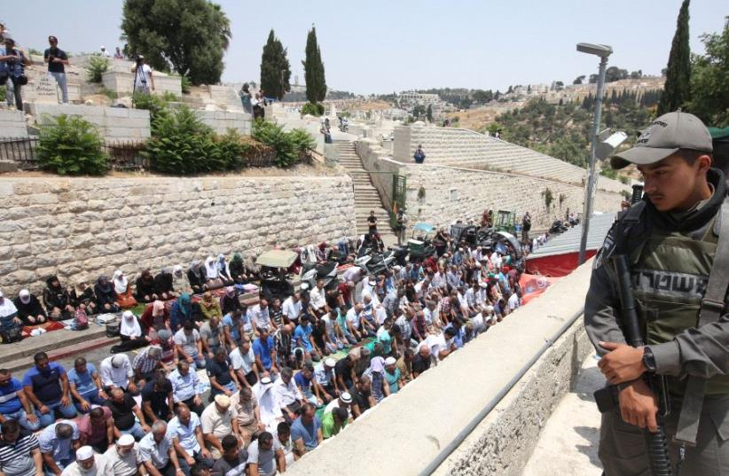 An Israeli soldier looks over a massive prayer session outside the Lions' Gate in Jerusalem, July 2017 (photo credit: MARC ISRAEL SELLEM/THE JERUSALEM POST)