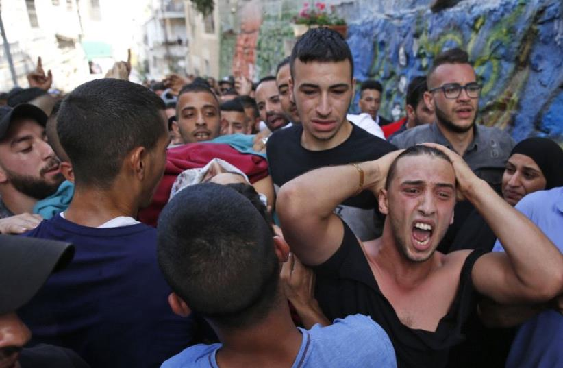 Palestinian relatives of Mohammed Abu Ghannam, who was shot dead during clashes with Israeli forces, mourn during his funeral in the A-Tur area of east Jerusalem, on July 21, 2017. (photo credit: AHMAD GHARABLI / AFP)