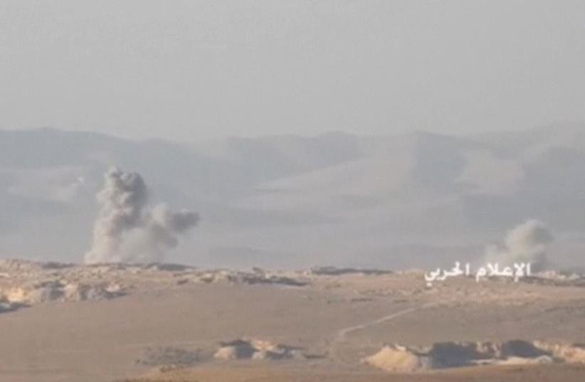 A still image taken on July 21, 2017 from an undated footage by Hezbollah Military handout shows smoke rising at an unidentified location at the Syrian-Lebanese frontier.  (photo credit: REUTERS)