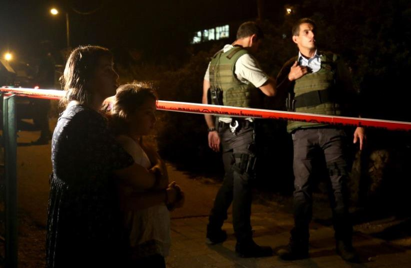 Israeli comfort each others outside the home, where a Palestinian broke in the day before and stabbed four Israelis killing three of them, in the Jewish settlement Neve Tsuf (Halamish), in the West Bank, on July 22, 2017 (photo credit: GALI TIBBON / AFP)