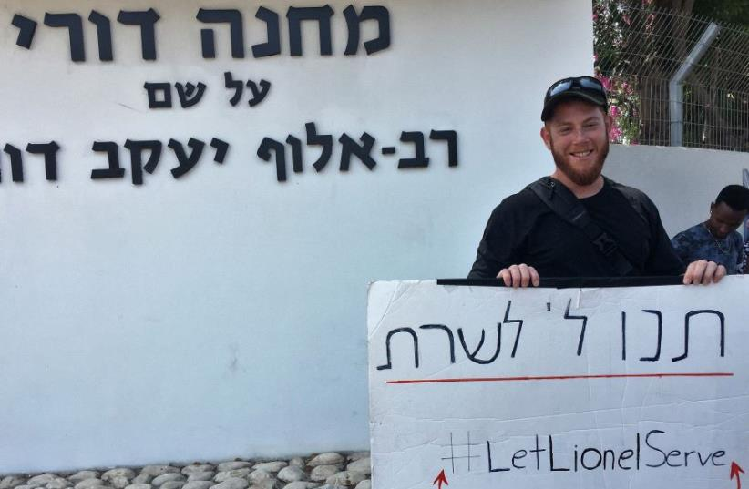 31 year old Lionel Kalles is standing outside the IDF induction center in Ramat Gan with a sign calling on the army to let him serve.  (photo credit: ANNA AHRONHEIM)