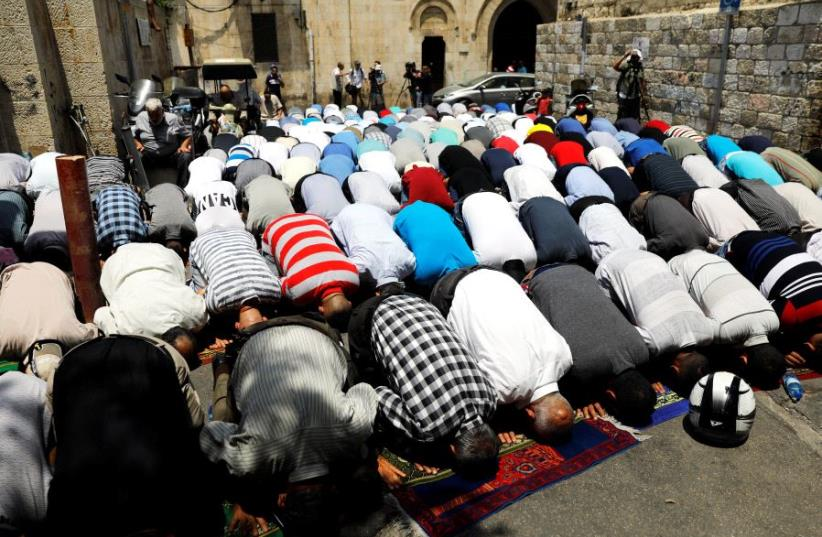 Palestinian men pray outside the Temple Mount after Israel removed the new security measures there, in Jerusalem's Old City July 25, 2017.  (photo credit: REUTERS)