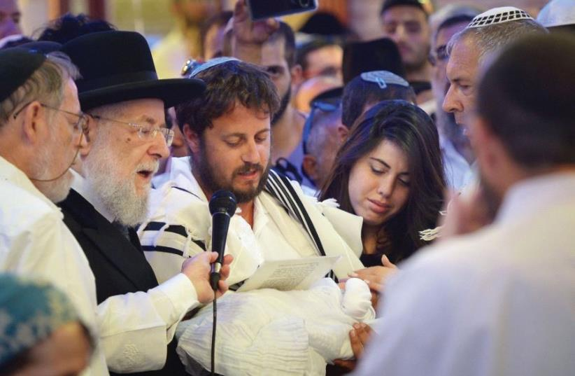 EIGHT-DAY-OLD Ari Yosef Salomon is held by his father, Shmuel, as the infant's mother, Chen, looks on and Rabbi Israel Meir Lau (second left) officiates at the brit in El'ad, July 27, 2017. (photo credit: FLASH90)