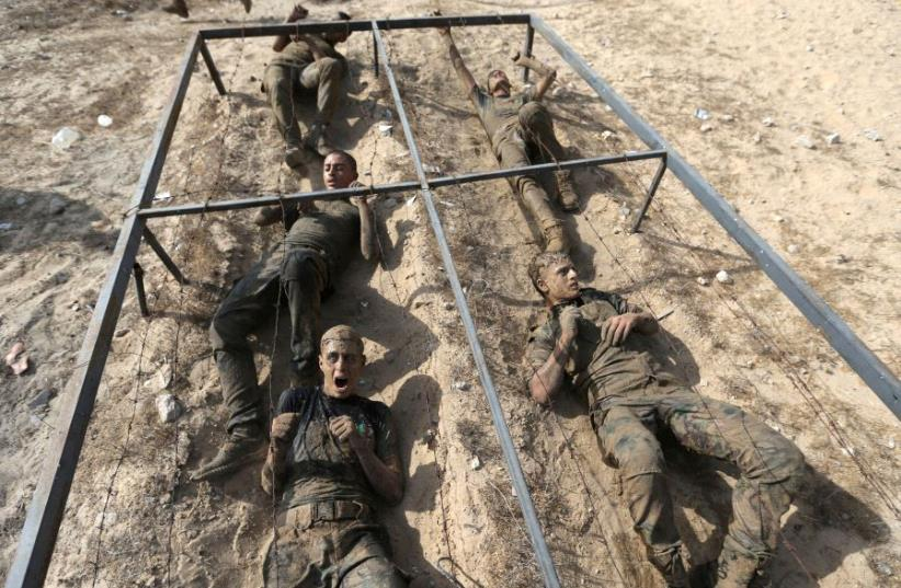 Young Palestinians crawl under an obstacle during a military-style exercise at a Hamas summer camp in Rafah in the southern Gaza Strip July 27, 2017. (photo credit: REUTERS)