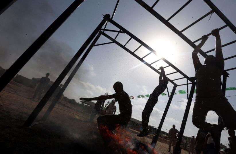 Young Palestinians swing across monkey bars over fire during a military-style exercise at a Hamas summer camp in Rafah in the southern Gaza Strip July 27, 2017.  (photo credit: REUTERS)