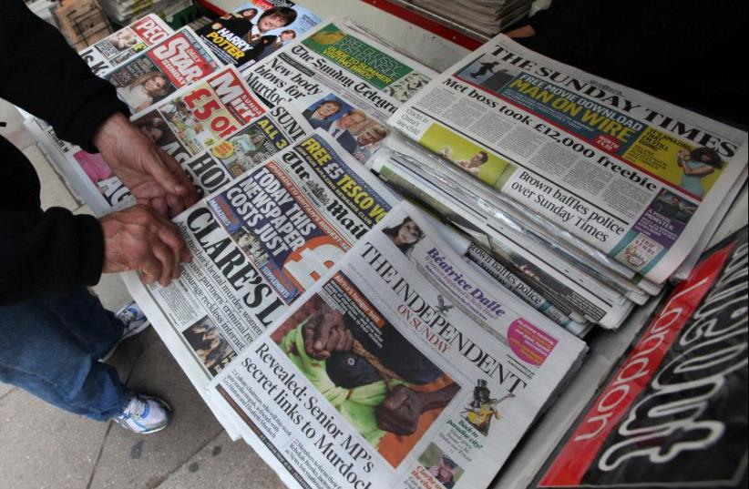 A man buys a Sunday newspaper at a news stand in London July 17, 2011. (photo credit: REUTERS/SUZANNE PLUNKETT)