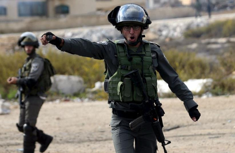 An Israeli border policeman shouts at journalists during clashes with between Israeli troops and Palestinian protesters near the Jewish settlement of Bet El, near the West Bank city of Ramallah October 30, 2015. (photo credit: REUTERS)