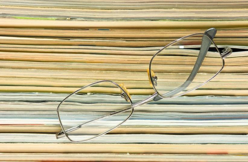 glasses on the background of the stack of magazines (photo credit: INGIMAGE)