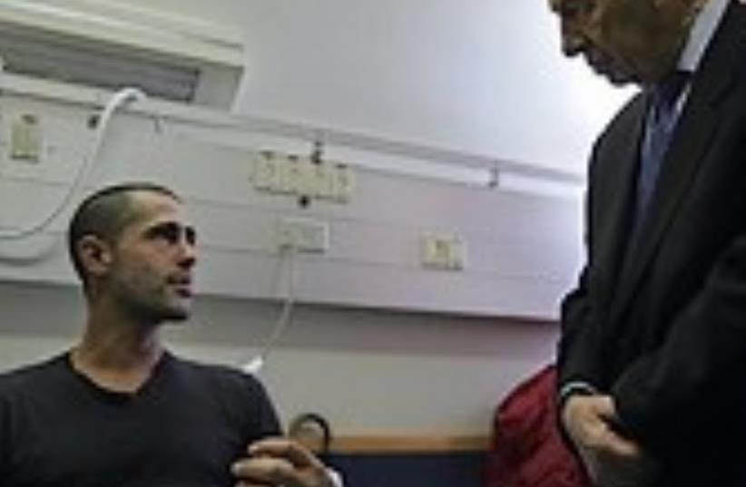 peres with soldier at hospital 88 ap (photo credit: AP)