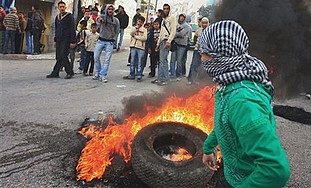 A masked Palestinian youth stands next to a burnin