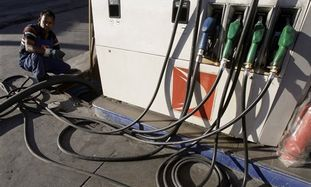 Worker filling a gasoline pump.